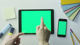 Designer is Using Tablet and Mobile Phone with Green Screen. Great For Mock-up Usage.