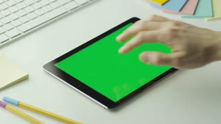 Designer is Using Tablet with Green Screen in Landscape Mode.