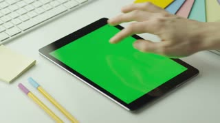 Designer is Using Tablet with Green Screen in Portrait Mode.