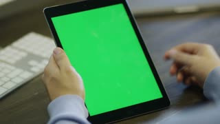Designer using Digital Tablet with Green Screen at Work in Portrait Mode.