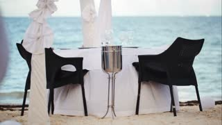 Dining outdoor on resort. Served empty table with white table cloth and black chairs standing by the sea on the beach