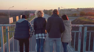 Diverse family of four stand at railing on walkway bridge and laugh as cars pass beneath