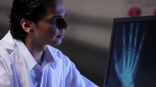 Doctor looking at x-ray image of a hand on a computer, dolly shot