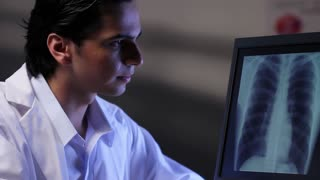 Doctor looking at x-ray image of chest on a computer, dolly shot.