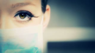 doctor or nurse woman with blue surgical mask showing her eyes and eyelashes