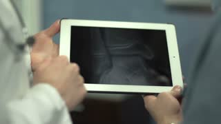 Doctor showing patient's knee on tablet