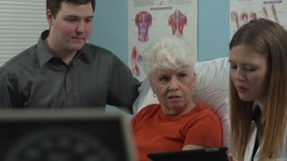 Doctor showing the patient and her grandson a chart on a tablet.