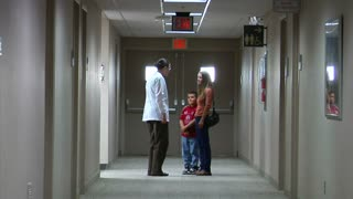 Doctor Speaking To Mom And Son In Hallway