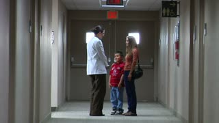 Doctor Speaking With Mom And Son In Hallway
