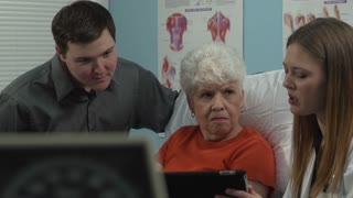 Doctor talking to patient and her grandson using a tablet to show her condition. Dollies to the right