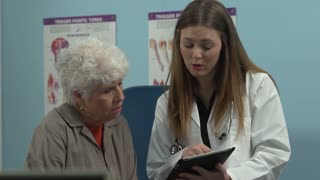 Doctor talking to patient using a tablet to explain her condition