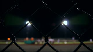 Dolly behind a fence viewing a high school football team as they warm up for a night time game.