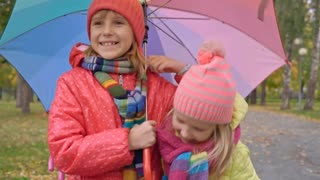 Dolly-like shot with tilt down of blond little girls with big umbrella with rainbow print walking along pavement in park and hugging