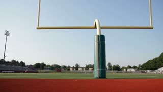Dolly of a football field with a yellow goalpost in the foreground.
