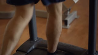 Dolly shot of a man running on treadmill with following focus on electronic display