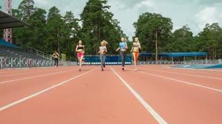 Dolly shot of beautiful smiling women in sportswear jogging along stadium track in summer