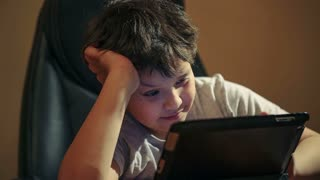 Dolly shot of boy using tablet PC sitting at the table