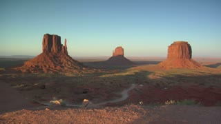 Dolly Shot Of Couple Sitting On Rocks Overlooking Monument Valley