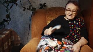 Dolly shot of elderly woman receiving a call and talking while sitting in the armchair at home in the evening