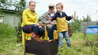 Dolly shot of mother, son and grandfather by the fire in the yard. Boy throwing firewood into the fire, mother applauding