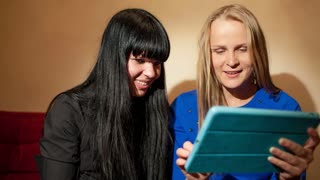 Dolly shot of two attractive young woman blonde and brunette reading a tablet-pc smiling as they look at information or photos on the screen