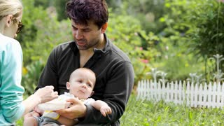 Dolly shot of young parents feeding baby outdoor. Father holding a kid, mom feeding him, then adjusting his clothes
