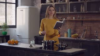 domesticity in modern life. Adult woman cooking and reading book with recipe on kitchen. Businesswoman wearing in casual elegant dress at home standing near cooker stir slowly soup