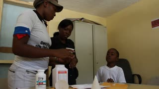 Dr Gives Medicine To Child  Thein Haitian Clinic