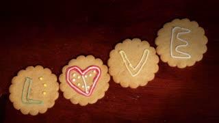 Drawing on ginger cookies. The word love.