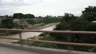 Driving Over A Bridge With River In Haiti