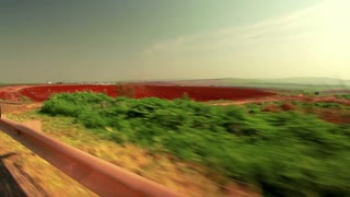 Driving Past Strip of Greenery and Red Field 3