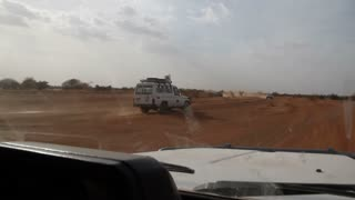 Driving Through Desert Near Land Cruiser