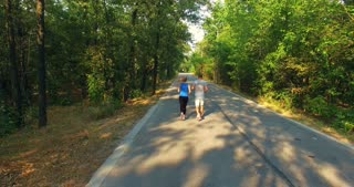 Drone clip of smiling sportwoman and sportsman running along countryside road in sunny forest