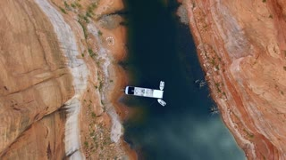 Drone shot straight down onto a houseboat surrounded by canyons in Lake Powell Utah