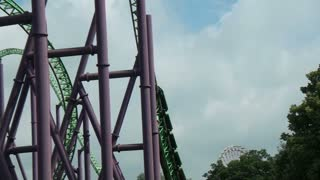 Drops and Turns around Green and Purple Roller Coaster