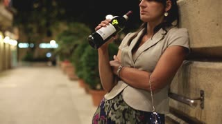 Drunk couple with bottle of wine standing on street in the evening
