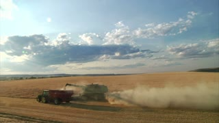 Dusty Field As Combine Harvests Grain
