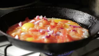 Egg frying in a pan. Adding onion slices.