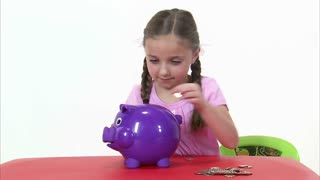 Eight Year Old Girl Putting Money in Piggy Bank 2
