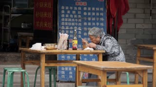 Elderly Chinese Lady having Lunch