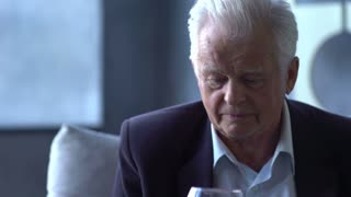 elderly man drinking wine at home