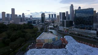Elevated dusk to night view over the Entertainment district of Clarke Quay, the Singapore river and City Skyline, South East Asia, Time lapse
