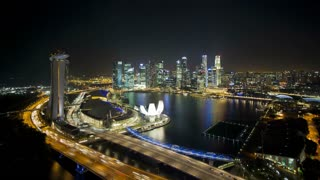Elevated illuminated downward view over the City Centre and Marina Bay, South East Asia, Time lapse