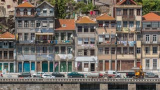 Embankment and traditional quaint houses in the old, vintage and touristic ribeira district of Porto at sunny day timelapse, Portugal