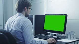 Engineer is Working on Computer. Display with Green Screen. Great for Mock-up Usage.