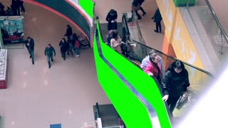 Escalator in Shopping mall with green screen advertising space. Crowds of people on escalator. Timelapse