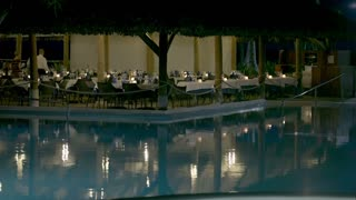 Evening time in luxurious restaurant near the swimming pool on tropical resort. Woman coming for dinner and taking her seat