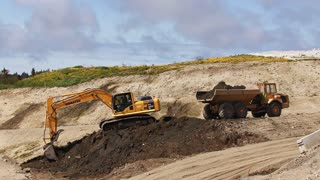 Excavator and Dump Truck Working at Job Site