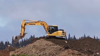 Excavator Scooping and Dumping on Dirt Pile