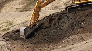 Excavator Scooping Dirt at Job Site